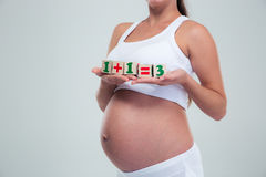 Pregnant woman holding bricks with equation Royalty Free Stock Photography