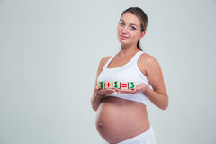 Pregnant woman holding bricks with equation Stock Image