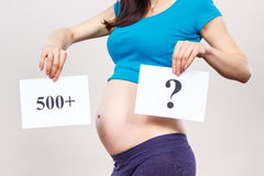 Pregnant woman holding card with inscription 500+ and question mark, social program and policy in Poland Stock Photos