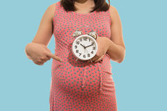 Pregnant woman holding clock. It's time. Royalty Free Stock Photo