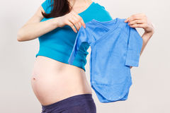 Pregnant woman holding clothing for newborn, expecting for baby Stock Photos