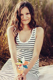 Pregnant woman holding colorful windmill on forest background.  Royalty Free Stock Photography