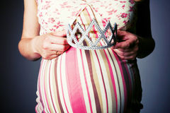 Pregnant woman holding crown under stomach Stock Photo