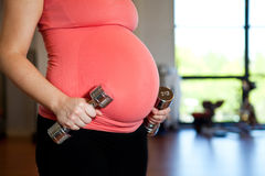 Pregnant woman holding dumbbells Stock Photos