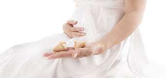 Pregnant woman holding fortune cookie. With blank paper for massage Royalty Free Stock Photography