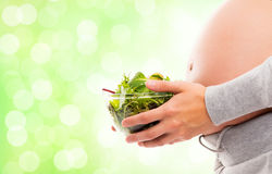 A pregnant woman holding a fresh green salad Stock Photo