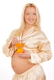 Pregnant woman holding fruit. Nine month. Royalty Free Stock Image
