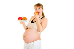 Pregnant woman holding fruits and eating apple Stock Photos