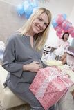 Pregnant Woman Holding Gift At A Baby Shower. Portrait of a happy pregnant women holding gift at a baby shower stock images