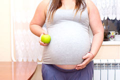 Pregnant woman holding a green apple in his hand next to the belly. Diet for pregnant women. Stock Images
