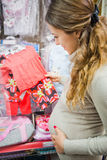 Pregnant woman holding hand baby clothes Stock Photos
