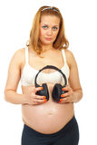 Pregnant woman holding headphones Royalty Free Stock Photos