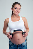 Pregnant woman holding headphones on belly. Happy pregnant woman holding headphones on belly isolated on a white background Stock Photo