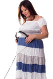 Pregnant woman holding headphones at her belly Royalty Free Stock Image