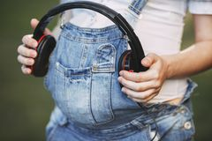 Pregnant woman holding headphones on her belly royalty free stock photography