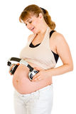 Pregnant woman holding headphones on her tummy Stock Photo