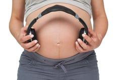Pregnant woman holding headphones over bump Stock Photos