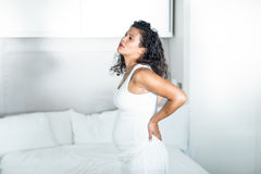 Pregnant woman holding her back while standing by bed Royalty Free Stock Image