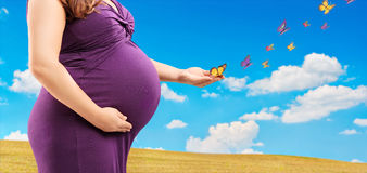 Pregnant woman holding her belly and butterflies on her hand, ou Stock Photo