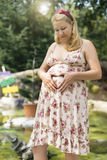 Pregnant woman holding her belly. In front of fountain Royalty Free Stock Images
