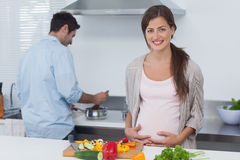 Pregnant woman holding her belly in the kitchen Royalty Free Stock Photography