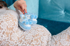 Pregnant woman holding her stomach at the knitted baby shoes royalty free stock photography