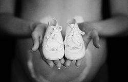 Pregnant woman holding little baby shoes in front. Of belly. Black and white photo Royalty Free Stock Photo
