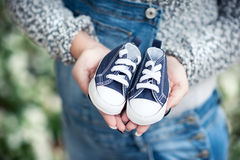 Pregnant woman holding little shoes for her baby Stock Images