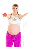 Pregnant woman holding measure tape and apple Stock Photography