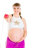 Pregnant woman holding measure tape and apple Stock Images