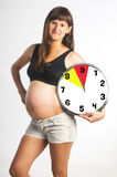 Pregnant woman holding months clock. Happy smiling pregnant woman on nineth month holding months clock isolated on white background Stock Photo