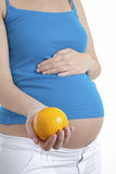 Pregnant woman holding orange Stock Photo