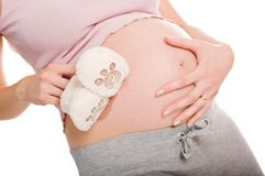 Pregnant woman holding pair of shoes for baby Royalty Free Stock Images
