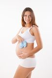 Pregnant woman holding pair of shoes for baby Royalty Free Stock Photography