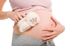 Pregnant woman holding pair of white  shoes Royalty Free Stock Image