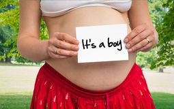 Pregnant woman holding paper with inscription: It`s a boy Stock Photos