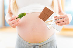 Pregnant woman holding pickle and chocolate Stock Photo