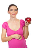 Pregnant woman holding red apple royalty free stock photography