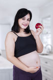Pregnant woman holding a red apple Royalty Free Stock Image