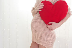 Pregnant woman is holding red heart near belly Stock Image
