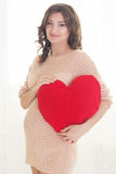 Pregnant woman is holding red heart Royalty Free Stock Images