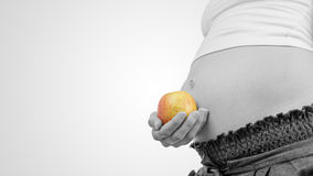 Pregnant woman holding a ripe apple Royalty Free Stock Photos