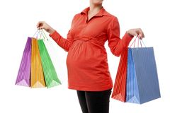 Pregnant woman holding shopping bags isolated Stock Images