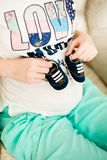 Pregnant woman holding small baby shoes Royalty Free Stock Images