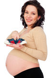 Pregnant woman holding small sneakers. Happy pregnant woman holding small sneakers Royalty Free Stock Images
