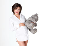 Pregnant woman holding soft toy. Pretty young woman carrying teddy bear. Free space for text. Stock Photos
