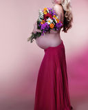 Pregnant woman holding spring flowers Royalty Free Stock Image