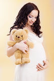 Pregnant woman holding teddy bear Stock Photography
