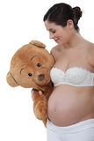 Pregnant woman holding teddy bear Stock Images