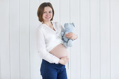 Pregnant woman holding a teddy bear Stock Photography